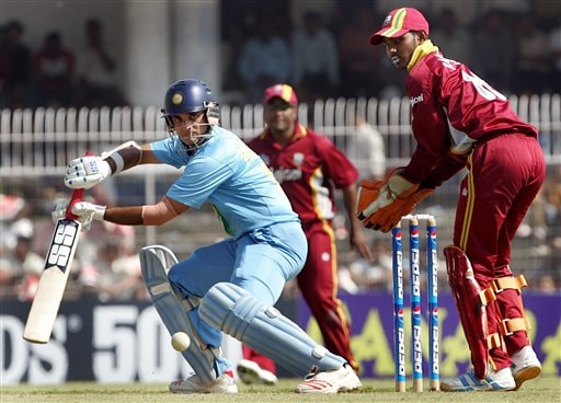 Sourav Ganguly, left, plays a shot as West Indies wicket keeper Ramdin Denesh, right, looks on during the first one day international cricket match in Nagpur