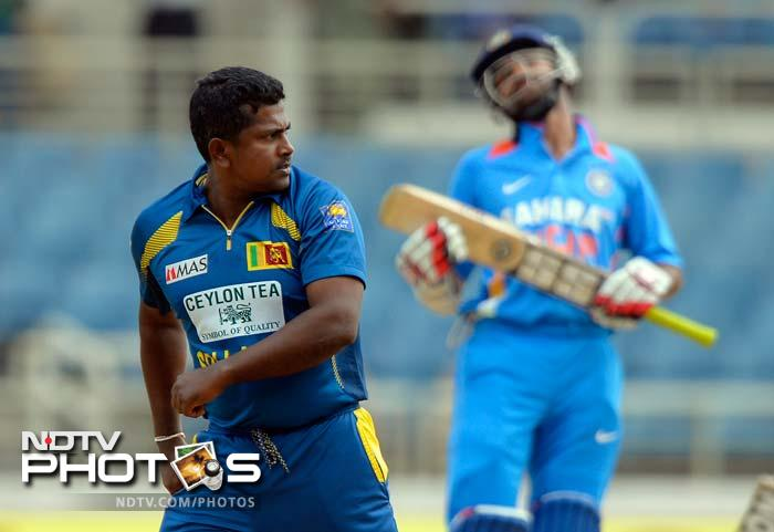 In reply, the in-form Indian batting failed to mount any fight as batsmen left in a rush. <br><br>Opener Shikhar Dhawan (24 off 42) is seen reacting after Rangana Herath (left) brought his innings to an end.