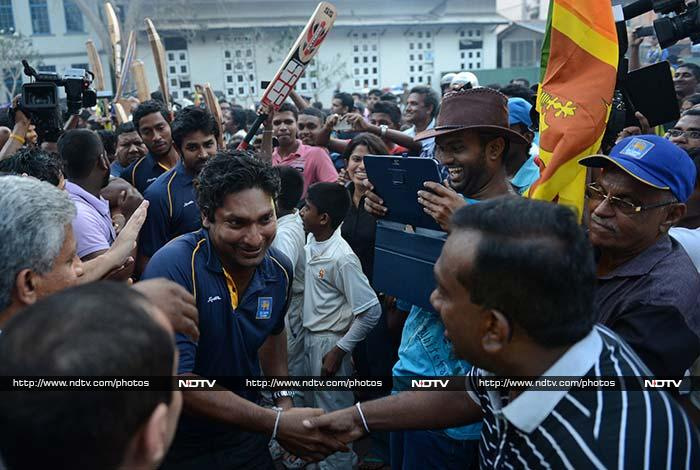 Sri Lankan Sports Minister Mahindananda Aluthgamage (R) shakes hands with Kumar Sangakkara as he and other cricketers return victorious to Colombo on March 9, 2014.