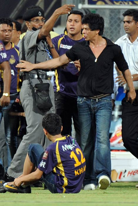 Shah Rukh Khan brushes aside a security guard directing his children Aryan and Suhana accompanying him off the playing field after the match.