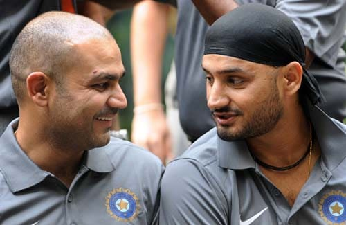 Virender Sehwag speaks with teammate Harbhajan Singh at the official team photo opportunity in Mumbai. (AFP Photo)