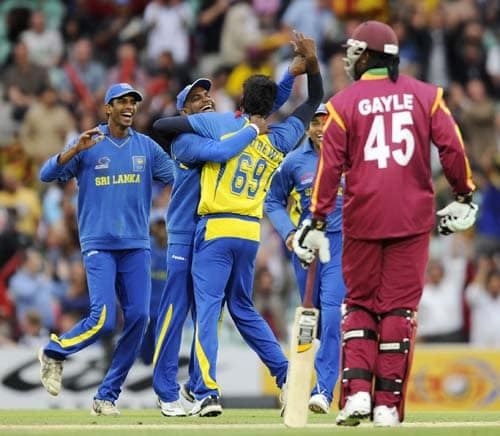 Sanath Jayasuriya celebrates after Angelo Mathews took the wicket of Dwayne Bravo as Chris Gayle watches during the ICC World Twenty20 semi-final match at the Oval. (AFP Photo)
