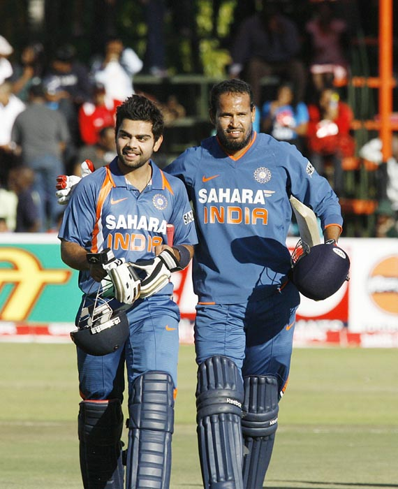 Indian batsman Virat Kohli and Yusuf Pathan walk off the field after India beat Zimbabwe by six wickets at Harare Sports Club in the first of the two matches of the Twenty 20 series . (AFP Photo)
