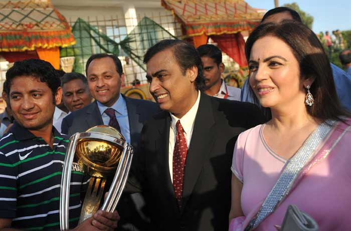 Indian cricketer Piyush Chawla, holding the Cricket World Cup trophy, is photographed with business tycoon Mukesh Ambani and wife Nita Ambani. (AFP Photo)