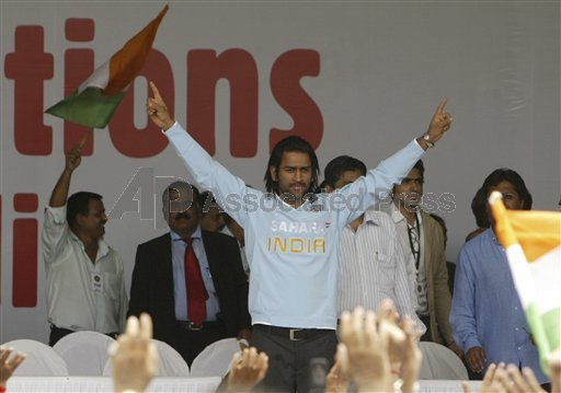 Dhoni gestures towards the crowd at the ceremony.