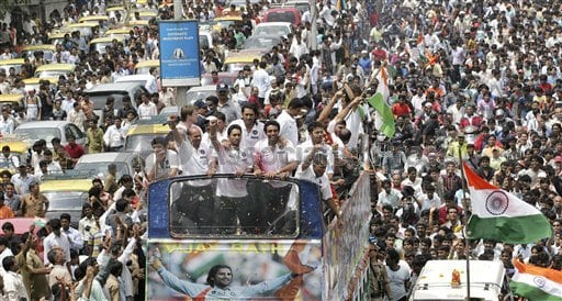 The Indian cricket team waves to fans from an open-top bus, center, as a crowd surrounds them during their 30-kilometre victory parade.