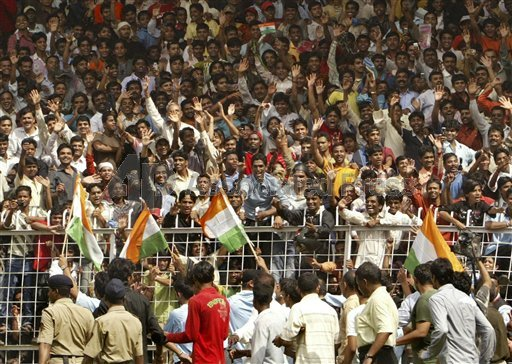 Cricket fans react as members of the Indian cricket Twenty 20(T20) team, hidden behind security personnel, walk past at the end of a ceremony.