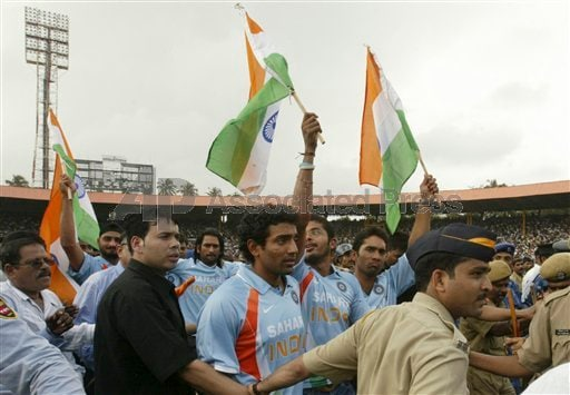 Indian cricket Twenty 20(T20) team members wave the Indian flag as they walk around the stadium.