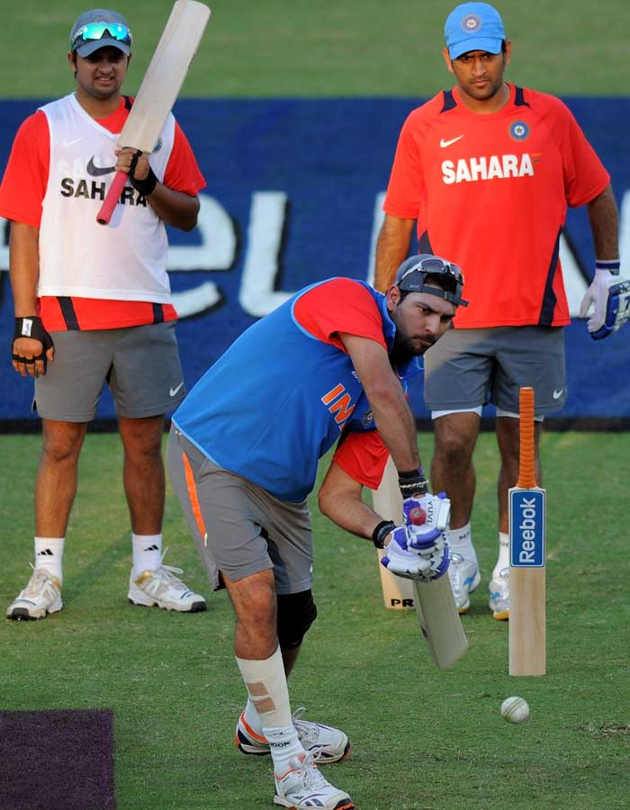 Indian cricket captain Mahendra Singh Dhoni and teammate Suresh Raina watch as Yuvraj Singh bats during a training session. (AFP Photo)