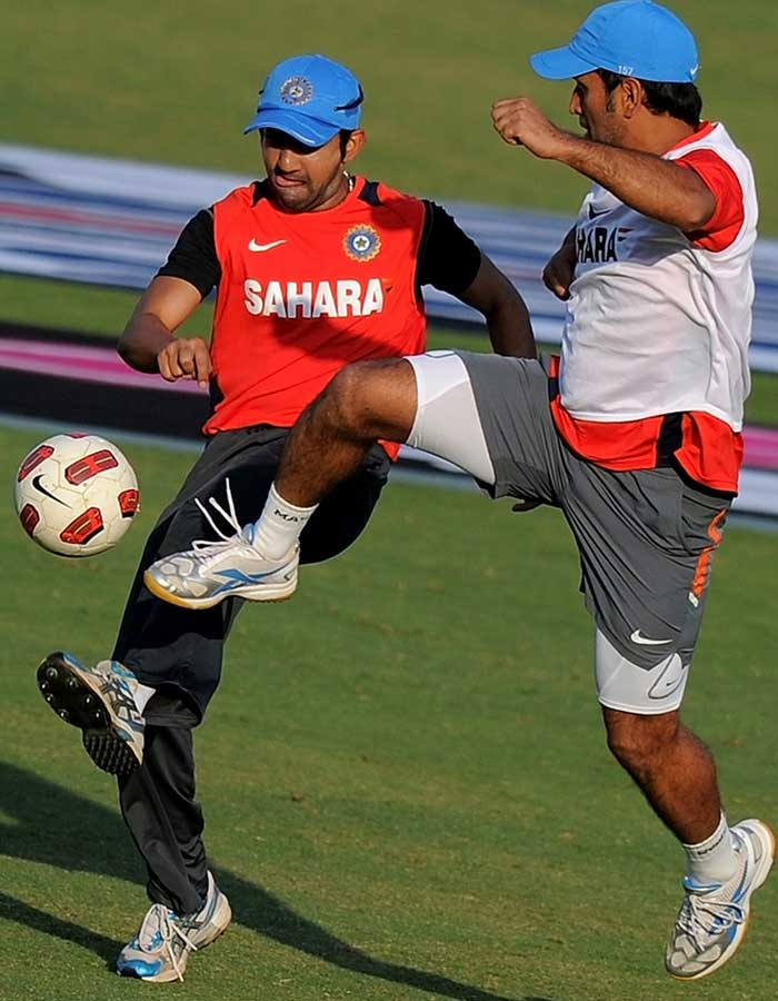 Indian cricket captain Mahendra Singh Dhoni and teammate Gautam Gambhir play football during a training session at the Feroz Shah Kotla Stadium. (AFP Photo)