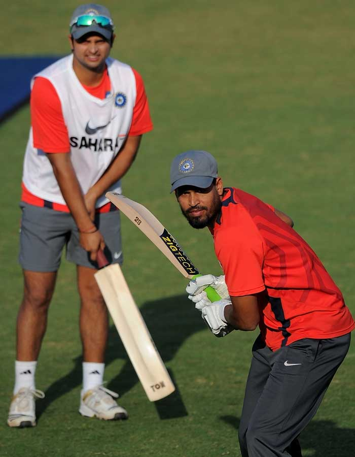 Indian cricketer Suresh Raina looks on as teammate Yusuf Pathan bats during a training session. (AFP Photo)