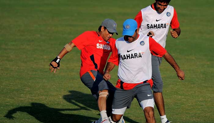 Indian cricketer Sachin Tendulkar tackles captain Mahendra Singh Dhoni as teammate Munaf Patel looks on during a training session. (AFP Photo)