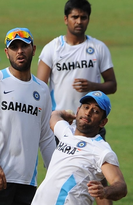 Indian cricket captain Mahendra Dhoni is watched by teammates Yuvraj Singh (L) and Vinay Kumar (TOP) as he delivers a ball during a training session.(AFP Photo)