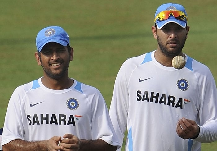 Indian cricket captain Mahendra Singh Dhoni (L) and teammate Yuvraj Singh share a light moment during a training session. (AFP Photo)