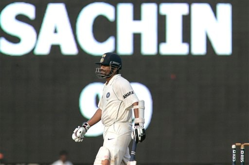 Sachin Tendulkar walks in front of a giant screen before making a century during the fifth day of the first Test cricket match between India and England in Chennai on Monday, December 15, 2008. (AP Photo)