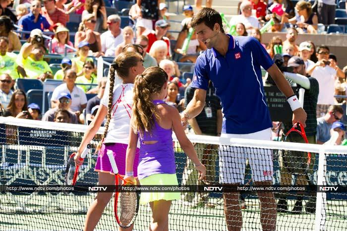 On the court, Novak Djokovic is seen here after a match against a child. He reportedly found the competition extremely stiff. <BR><BR>Image courtesy AFP and AP