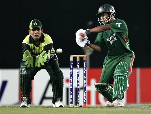 Bangladesh's Mohammad Ashraful, right, plays a shot as Pakistan's wicket keeper Kamran Akmal looks on during their first one-day international cricket match in Dhaka on Sunday, June 8, 2008.