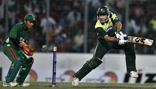 Misbah-ul-Haq, right, plays a shot as Bangladesh's wicket keeper Mushfiq Rahim looks on during their first one-day international cricket match in Dhaka on Sunday June 8, 2008. Pakistan had set a target of 233 runs in forty overs for Bangladesh, after the match started with a delay due to rain in Dhaka.