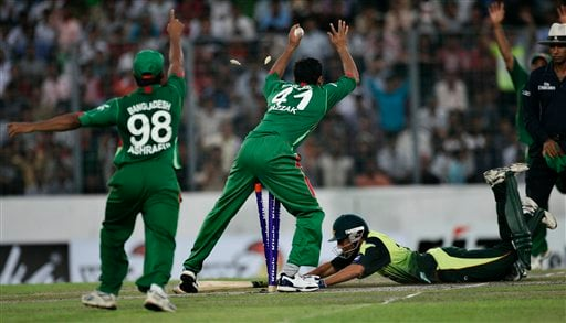 Bangladeshi players make a successful appeal for the dismissal of Younis Khan, diving to complete his run, during their first one-day international cricket match in Dhaka on Sunday, June 8, 2008. Pakistan had set a target of 233 runs in 40 overs for Bangladesh, after the match started with a delay due to rain in Dhaka.