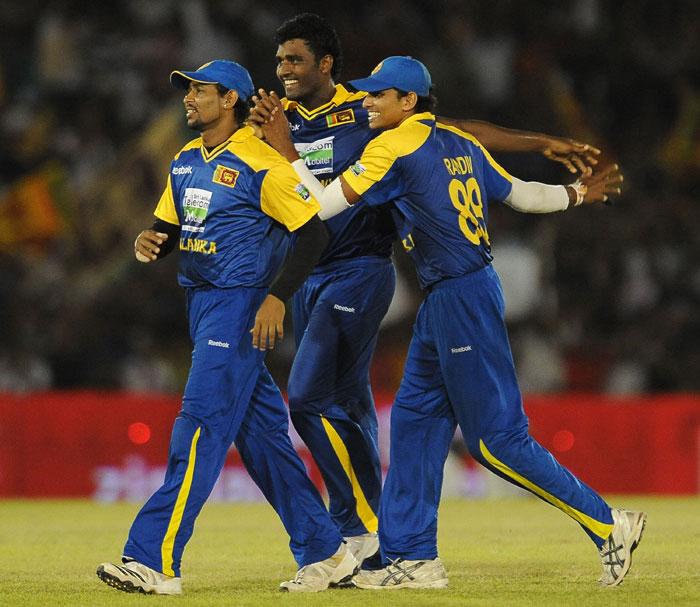 Thissara Perera celebrates with teammates Suraj Randiv and Tillakaratne Dilshan after he dismissed Virat Kohli during the final ODI of the Micromax tri-series between Sri Lanka and India in Dambulla. (AFP Photo)