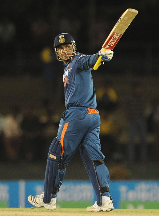 Virender Sehwag raises his bat to the crowd after scoring a half-century (50 runs) during the third ODI of the Micromax tri-series between Sri Lanka and India in Dambulla. (AFP Photo)