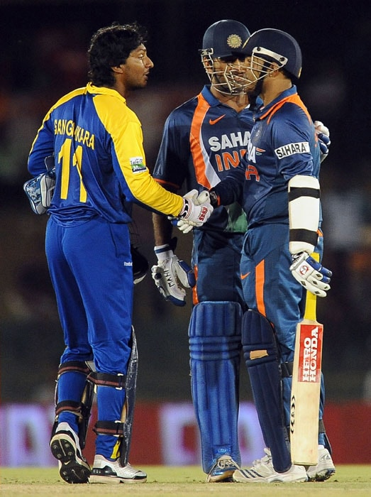 Kumar Sangakkara shakes hands with Virender Sehwag as Mahendra Singh Dhoni looks on at the conclusion of the third ODI of the Micromax tri-series between Sri Lanka and India in Dambulla. (AFP Photo)