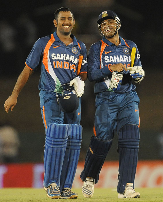 Mahendra Singh Dhoni and teammate Virender Sehwag walk back to the pavillion after victory in the third ODI of the Micromax tri-series between Sri Lanka and India in Dambulla. (AFP Photo)