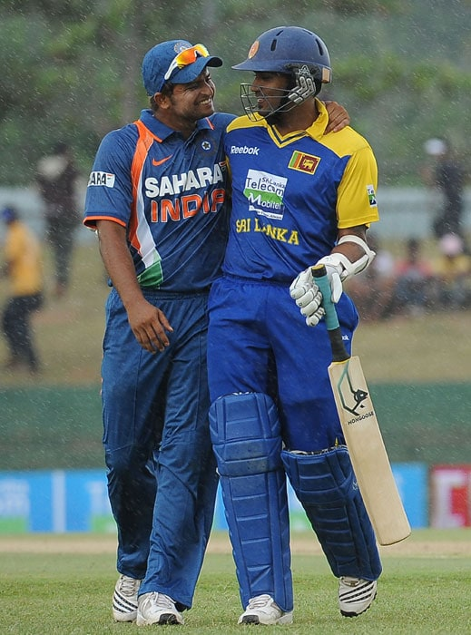 Suresh Raina and Chamara Kapugedera share a light moment as they walk off the field as rain stops play during the third ODI of the Micromax tri-series between Sri Lanka and India in Dambulla. (AFP Photo)