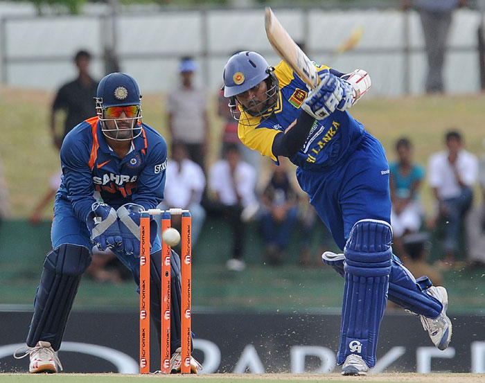 Tillakaratne Dilshan is watched by Mahendra Singh Dhoni as he plays a stroke during the third ODI of the Micromax tri-series between Sri Lanka and India in Dambulla. (AFP Photo)