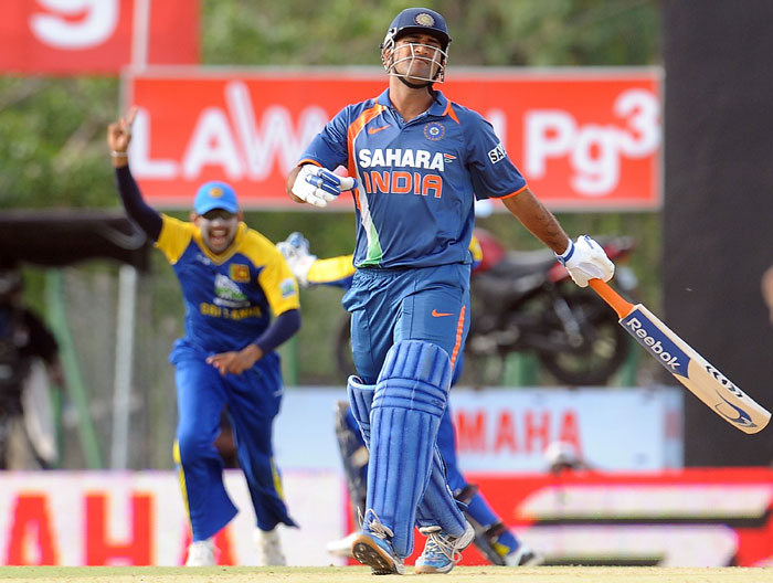 Mahendra Singh Dhoni reacts after Kumar Sangakkara takes a catch to dismiss him during the 5th ODI of the tri-series in Dambulla. (AFP Photo)