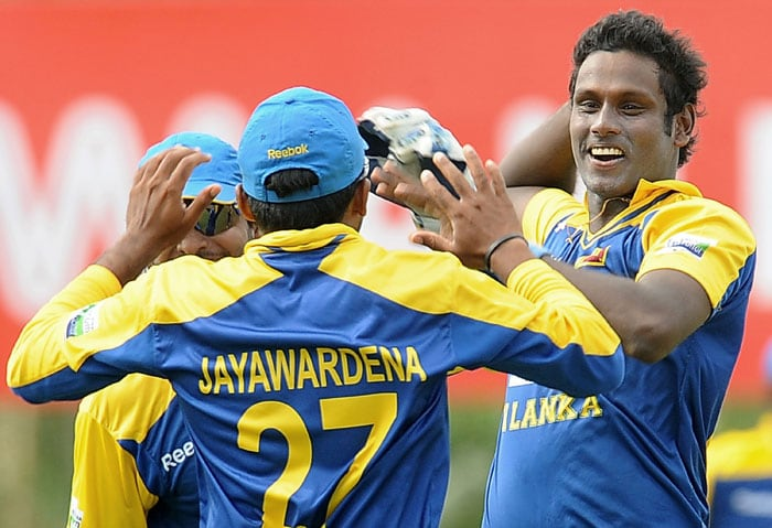 Angelo Mathews celebrates with teammate Mahela Jayawardene after he dismissed Rohit Sharma during the 5th ODI of the tri-series in Dambulla. (AFP Photo)