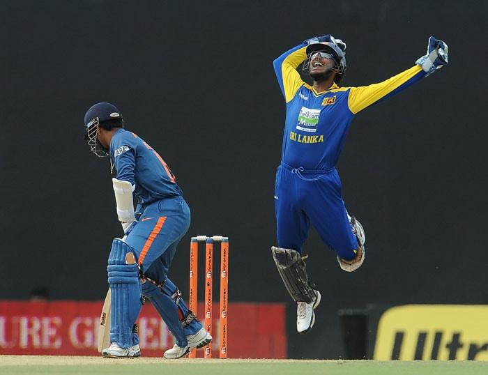 Kumar Sangakkara celebrates after taking a catch to dismiss Dinesh Karthik during the 5th ODI of the tri-series in Dambulla. (AFP Photo)