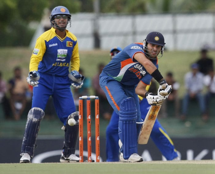 Yuvraj Singh looks on after playing a shot as Kumar Sangakkara watches during the 5th ODI of the tri-series in Dambulla. (AP Photo)