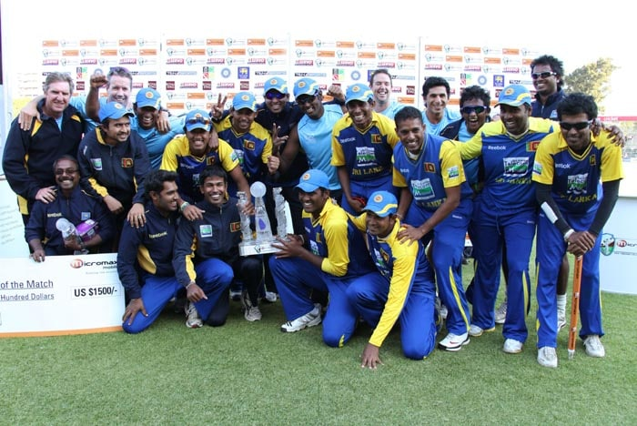 The Sri Lankan team poses with the trophy after they beat Zimbabwe by 9 wickets in the final of the tri-series at the Harare Sports Club. (AP Photo)