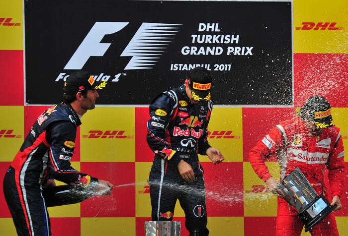 Red Bull Racing's Australian driver Mark Webber (L), his team-mate Sebastian Vettel (C) and Ferrari's Spanish driver Fernando Alonso spray champagne at Istanbul Park after finishing on the podium at the Turkish Formula One Grand Prix. (AFP PHOTO)
