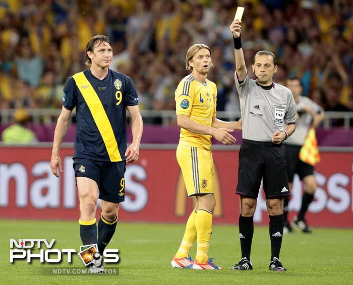 Sweden's Kim Kallstrom, left, gets a yellow card from the referee during the Euro 2012 Group D match between Ukraine and Sweden.