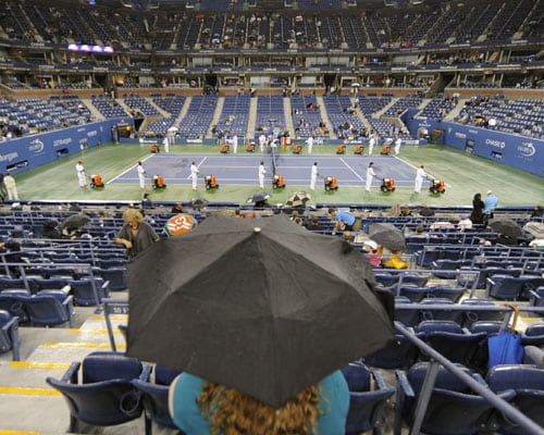 Workers blow dry center court as rain continues before the women's semi-final US Open match at the USTA Billie Jean King National Tennis Center in New York. (AFP Photo)