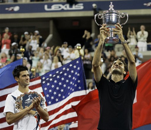 Novak Djokovic, left, of Serbia applauds as Roger Federer of Switzerland holds up the championship trophy after winning the men's finals at the US Open tennis tournament in New York, Sunday, Sept. 9, 2007.