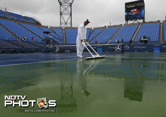 A worker dries the court at Louis Armstrong stadium during the US Open tennis tournament in New York. The start of play at the US Open is being delayed because of rain. (AP Photo)