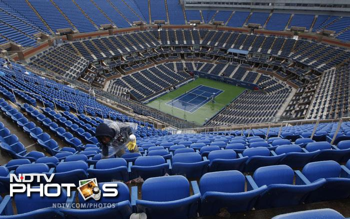Leah Gethers cleans up around the seats at Arthur Ashe Stadium during the US Open tennis tournament in New York. Rain is expected throughout the metropolitan area. (AP Photo)