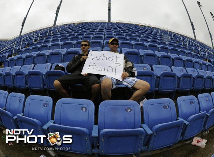 Tennis fans Art and Nate Scinta sit in the rain in the upper deck of Arthur Ashe Stadium as bad weather washed out the play at the 2011 US Open at the USTA Billie Jean King National Tennis Center in New York. (AFP Photo)