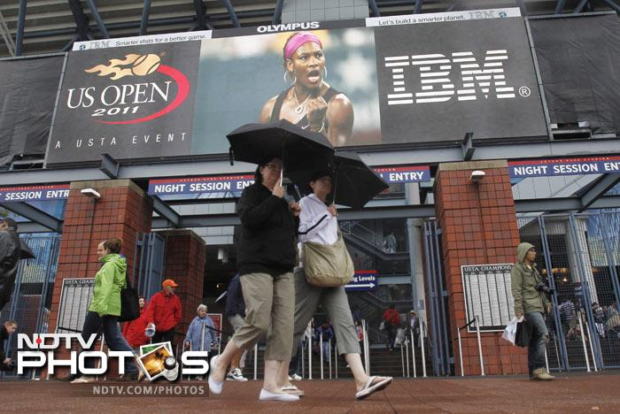 Fans walk near an entrance to Arthur Ashe Stadium during the US Open tennis tournament in New York. The US Tennis Association announced just after 1:30 p.m. that because of unfavorable forecasts, it would have to cancel both the day and night sessions, hoping to resume play at 11 AM on Wednesday. (AP Photo)