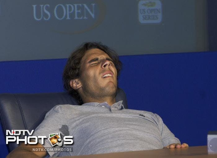 <b>Moment of the day: </b>Frozen by the leg cramps that simultaneously hit his right hamstring and thigh about two hours after he'd won his third-round match,World No. 2 Rafael Nadal rolled his head back, squeezed his eyes shut, covered his contorted face with his left arm and leaned awkwardly in the leather chair used by players during U.S. Open news conferences. (AP Photo)