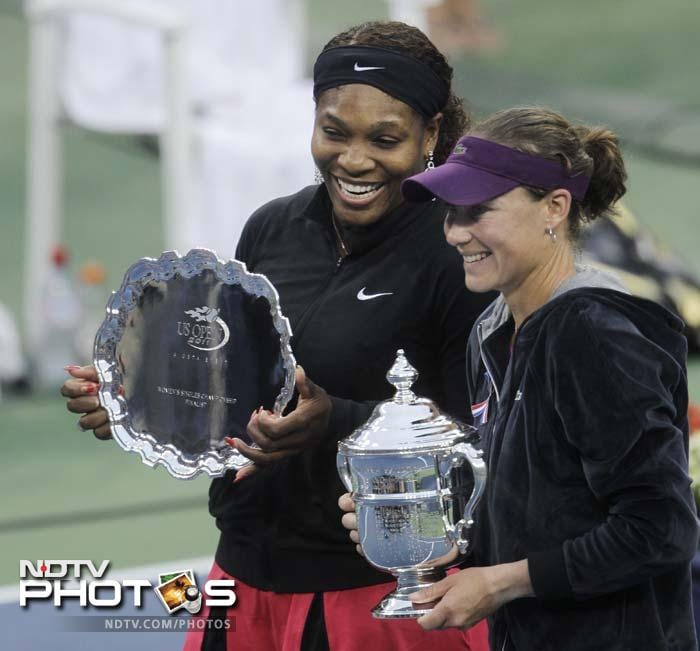 Samantha Stosur of Australia and Serena Williams pose with the trophies at the U.S. Open tennis tournament. (AP Photo)