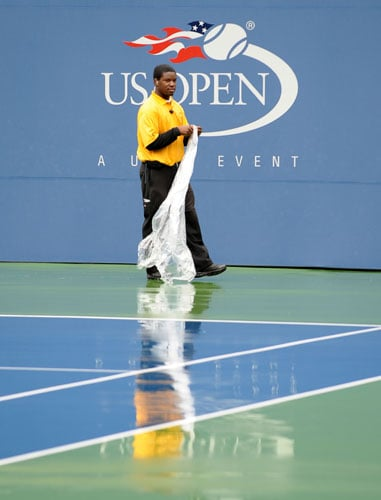 A security guard in Arthur Ashe Stadium puts on a poncho as rain delays the US Open at the USTA Billie Jean King National Tennis Center in New York. (AFP Photo)