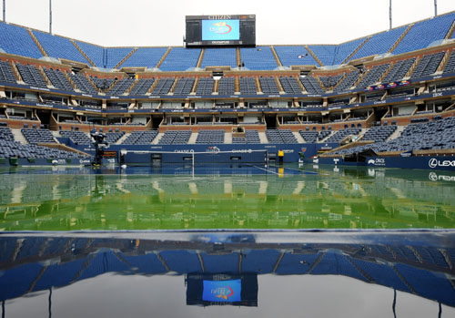 Arthur Ashe Stadium is reflected in puddles as rain delays the US Open at the USTA Billie Jean King National Tennis Center in New York. (AFP Photo)