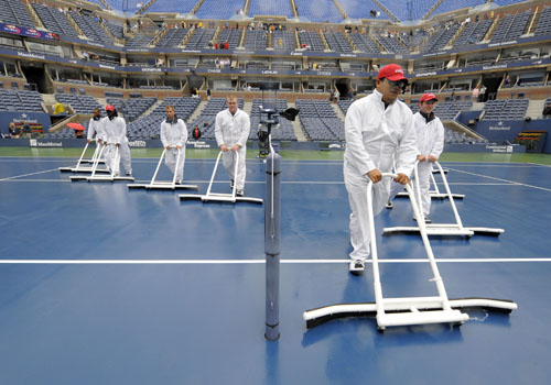 Court workers dry center court as rain delays the start of the women's semifinals US Open match at the USTA Billie Jean King National Tennis Center in New York. (AFP Photo)