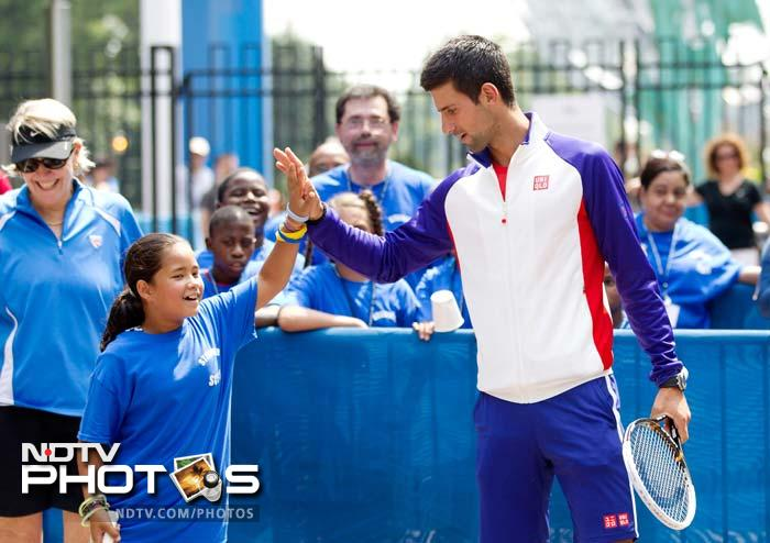 Novak Djokovic of Serbia high-fives a fan during a kids' clinic prior to the start of the 2012 U.S. Open.