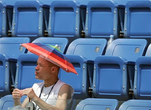 Sam Thompson from Elmira, NY, shades himself with an umbrella hat while watching a match between Justine Henin of Belgium and Tsvetana Pironkova of Bulgaria at the US Open tennis tournament in New York on Wednesday.
