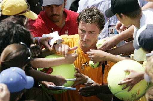 Marat Safin of Russia signs autographs after his match against Frank Dancevic of Canada at the US Open tennis tournament in New York, on Wednesday.